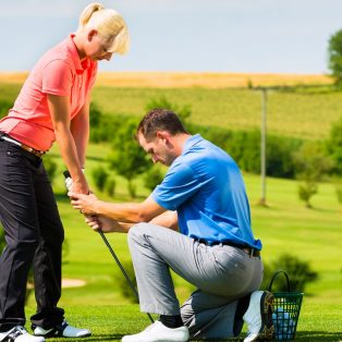 Young female golf player at Driving Range with a Golf Pro, she presumably does exercise